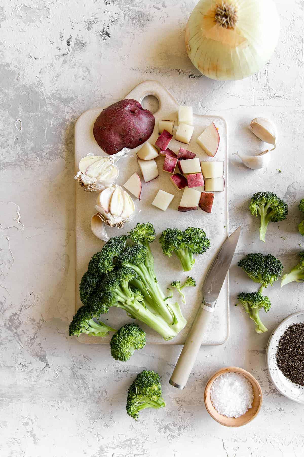 Broccoli cheddar soup ingredients on a cutting board.