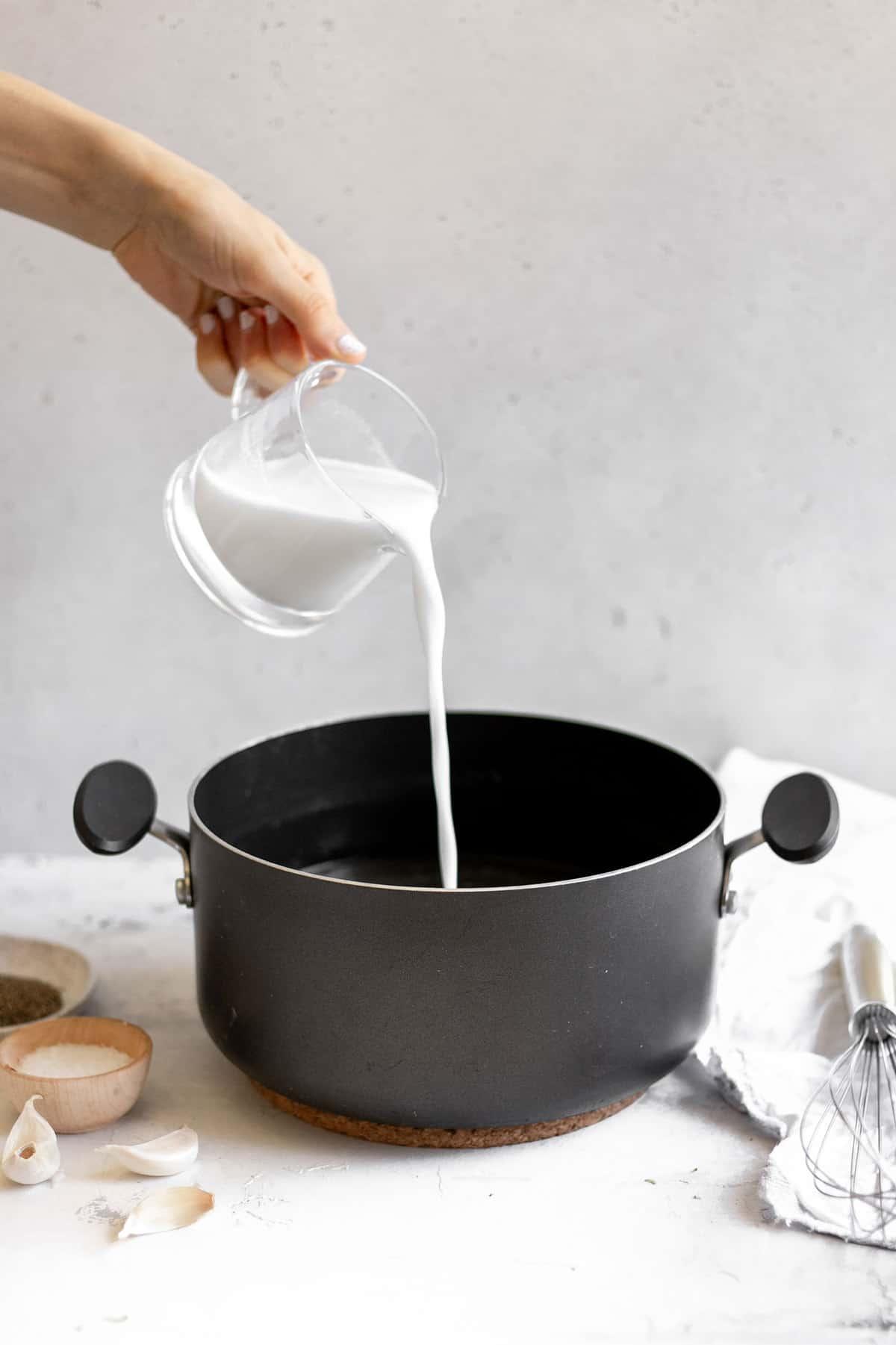 Pouring milk into a stock pot.