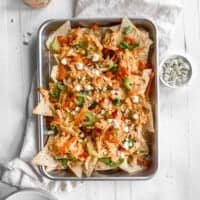 Buffalo chicken nachos on a baking sheet