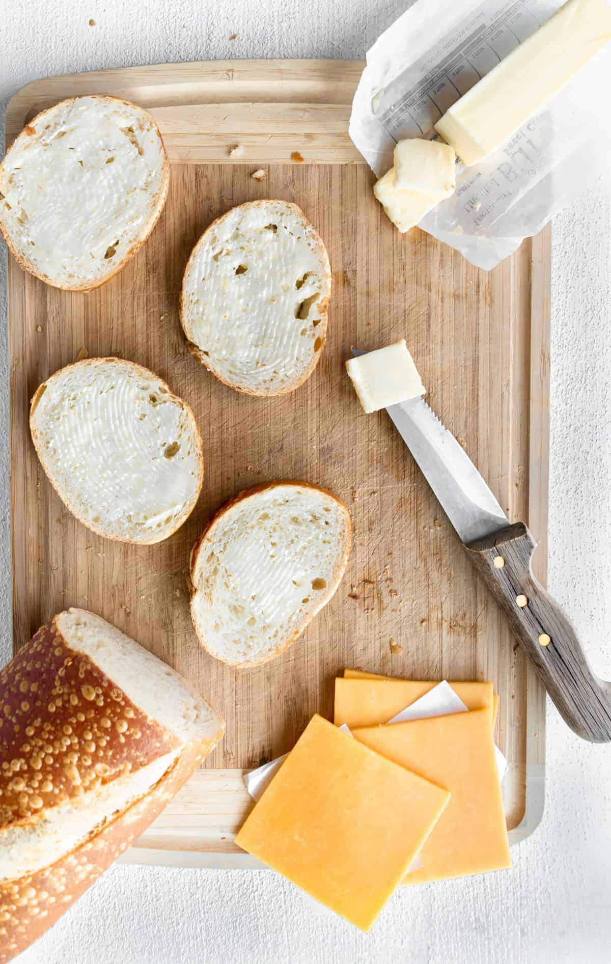 Italian bread, sliced cheese on cutting board