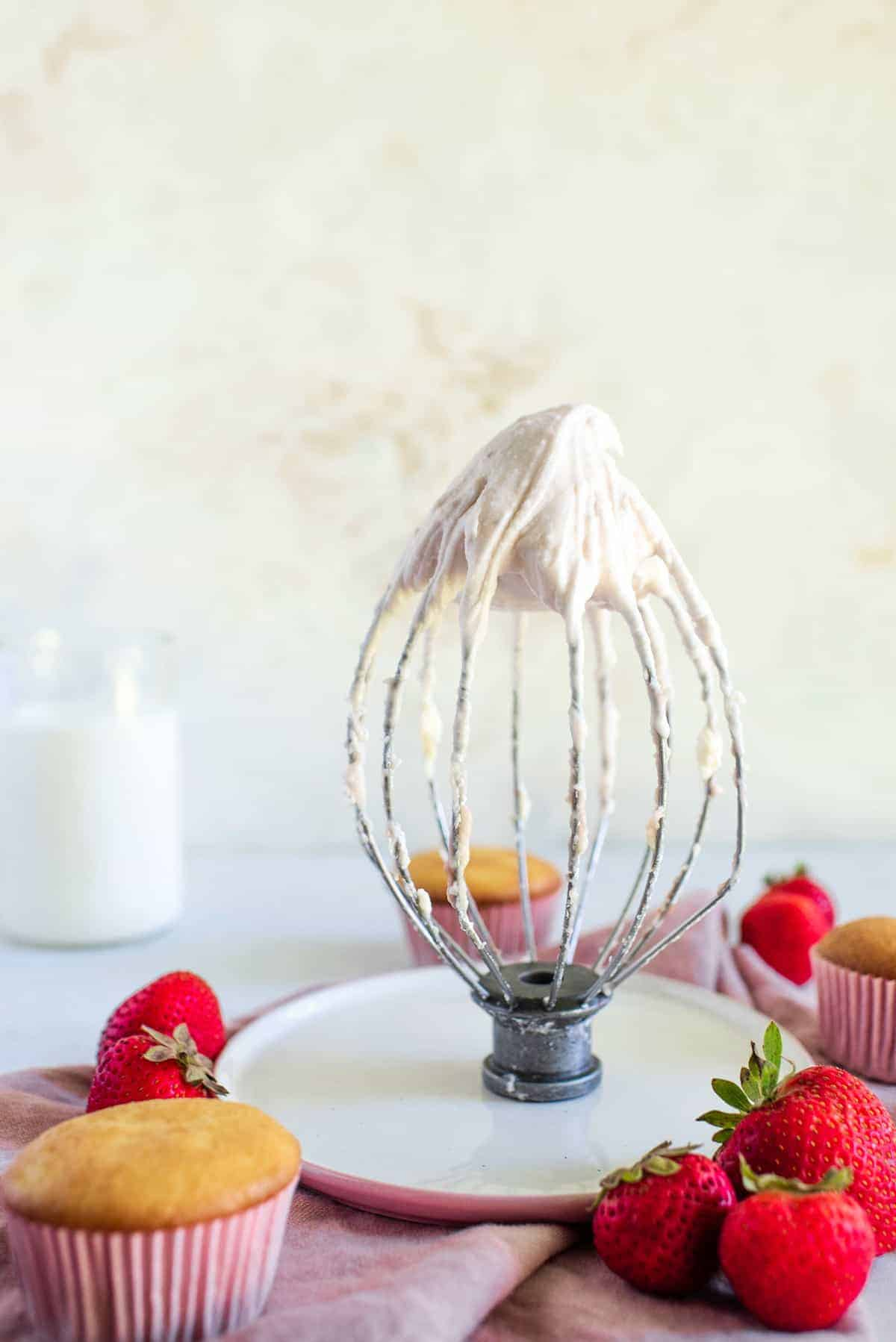 strawberry cream cheese frosting on a whisk