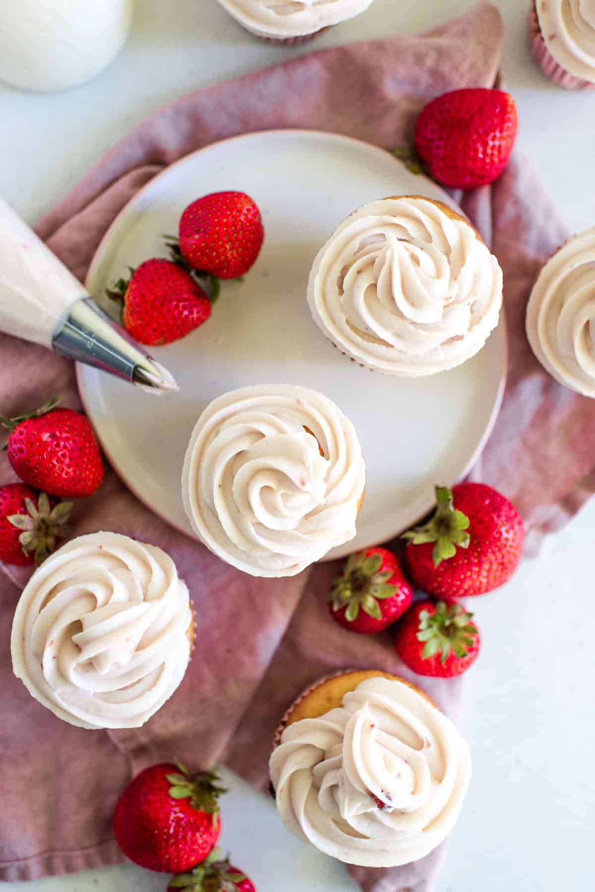 strawberry cream cheese frosting piped onto delicious cupcakes
