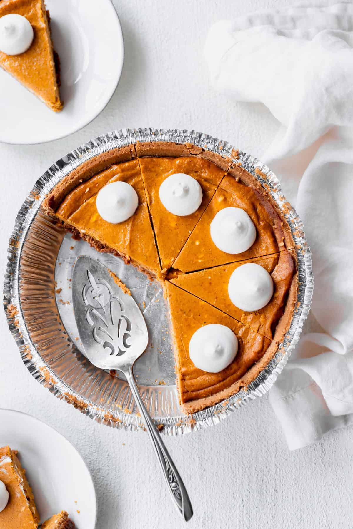 pumpkin cheesecake sliced in a pie tin