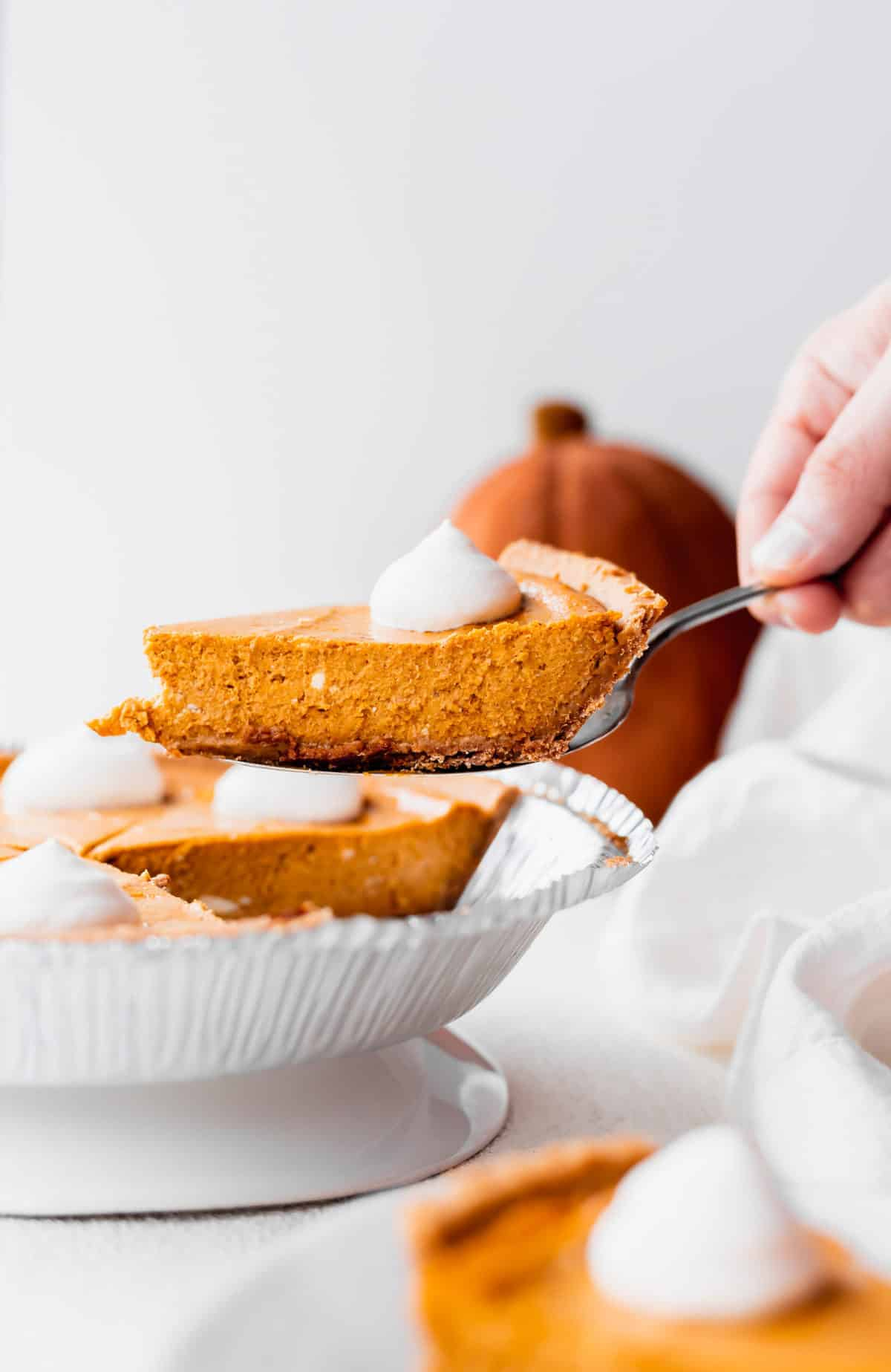 slice of pumpkin cheesecake being served to someone