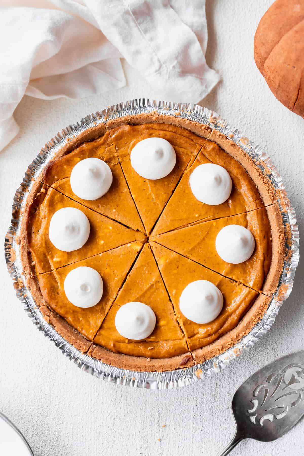 pumpkin cheesecake in a pie tin with dollops of whipped cream on the top