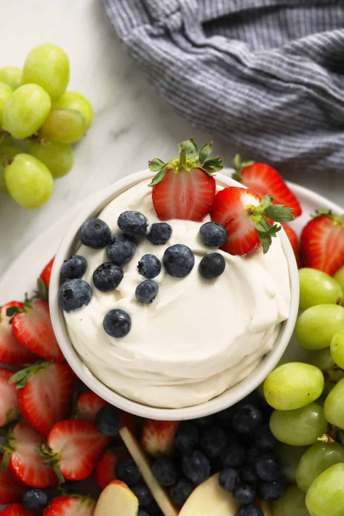 cream cheese fruit dip in a bowl surrounded by fresh fruit