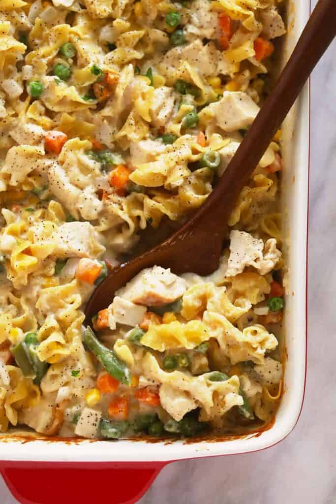 creamy chicken noodle casserole being scooped with a wooden spoon