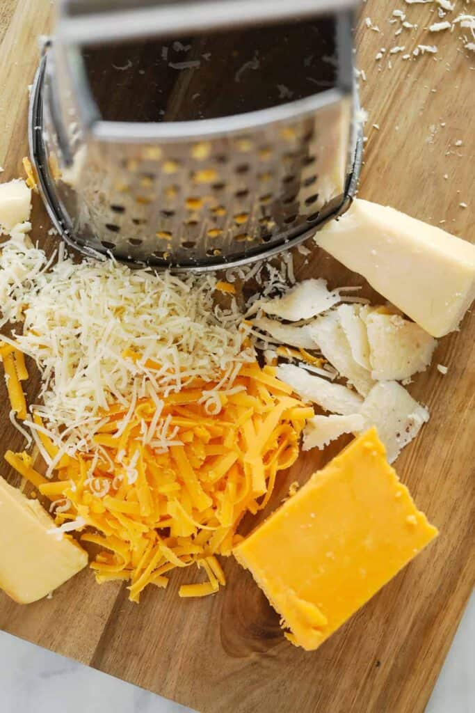 A box grater with different kinds of shredded cheese on the cutting board.