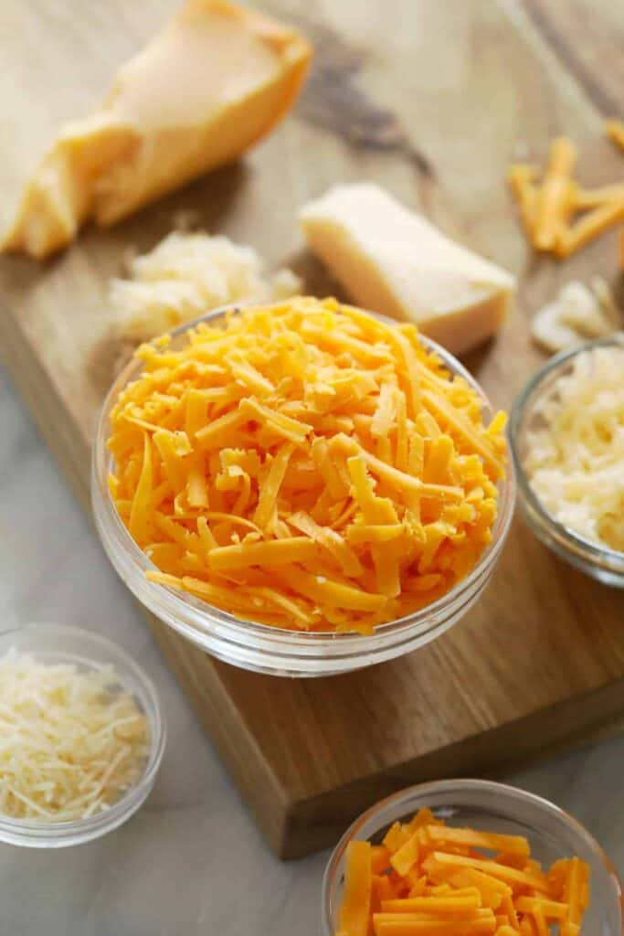 Many different grated cheeses on a cutting board.