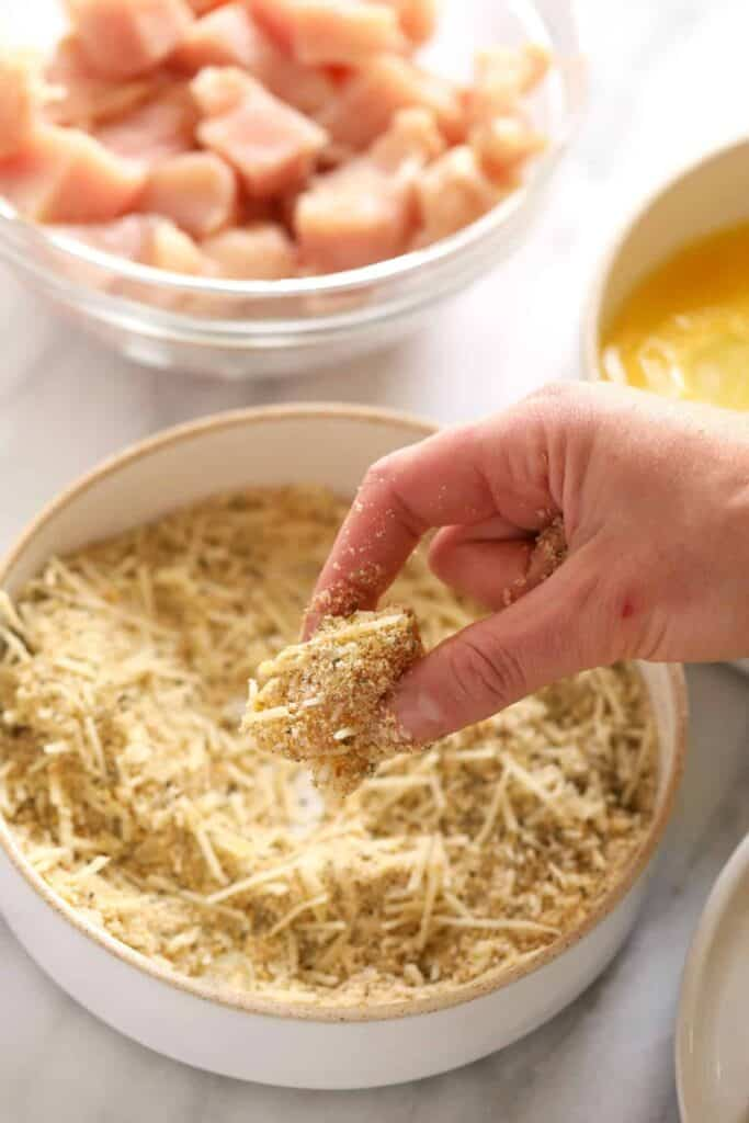 A hand dipping a piece of chicken into bread crumbs.