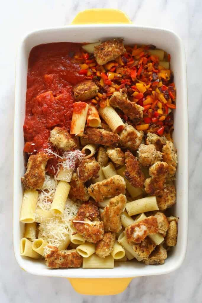 All the ingredients for the chicken parmesan casserole in a casserole dish.