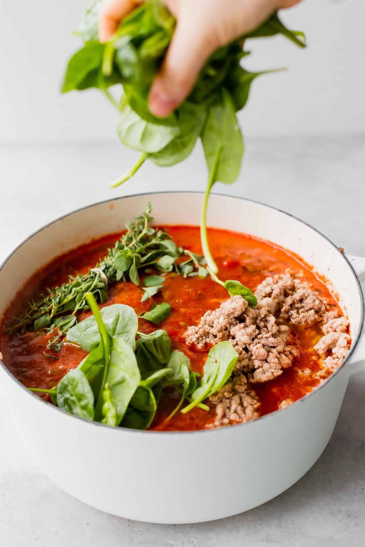 Throwing spinach into lasagna soup.