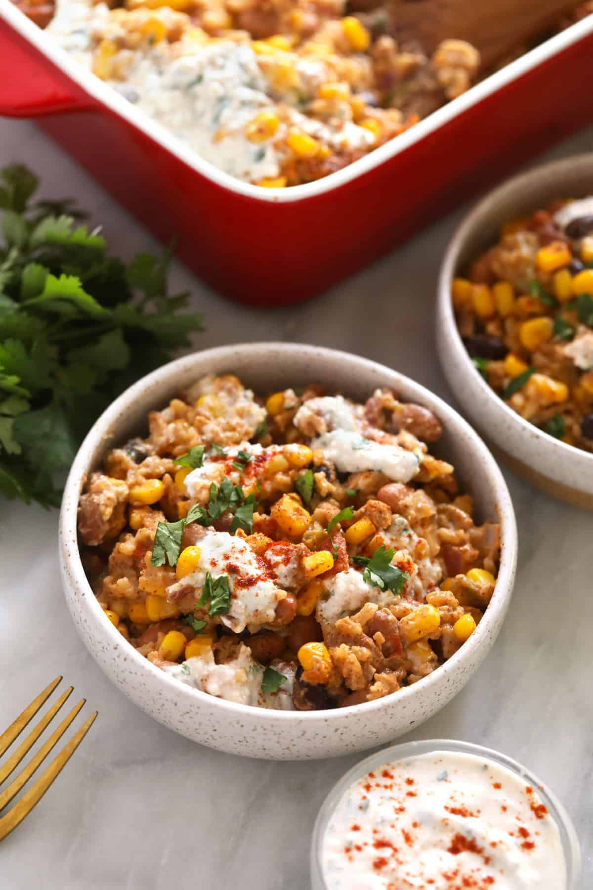 mexican street corn casserole in a bowl topped with chopped cilantro