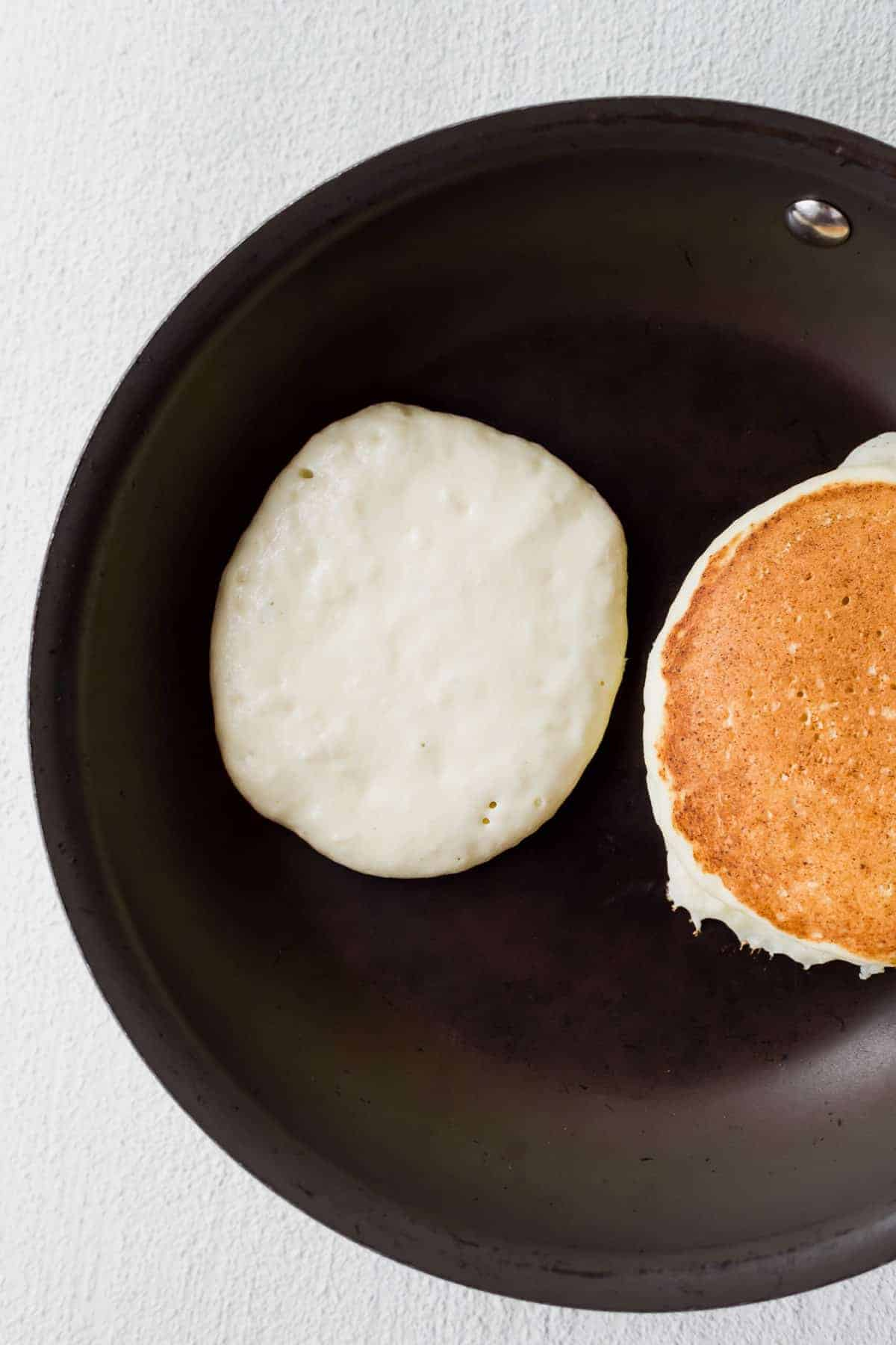 ricotta pancakes in a skillet looking perfectly golden brown