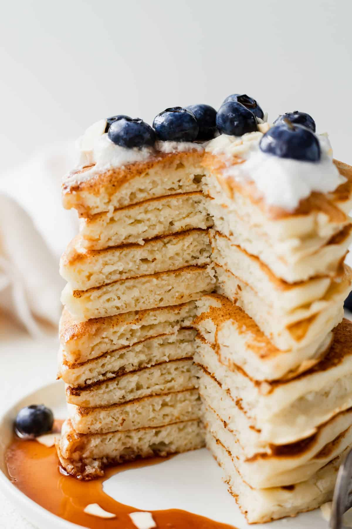 stack of ricotta pancakes with a slice taken out of it