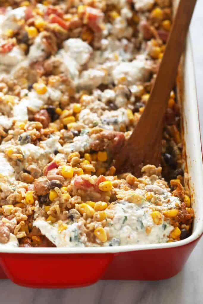 mexican street corn casserole with a cheese sauce drizzled on top