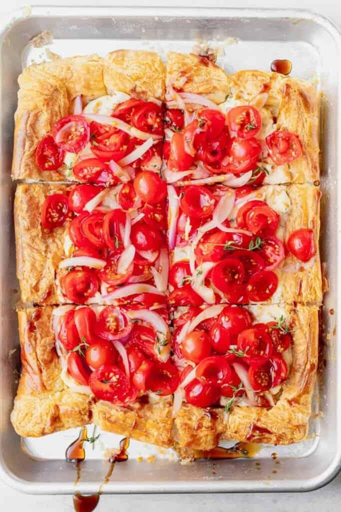 tomato tart on a baking sheet sliced into squares