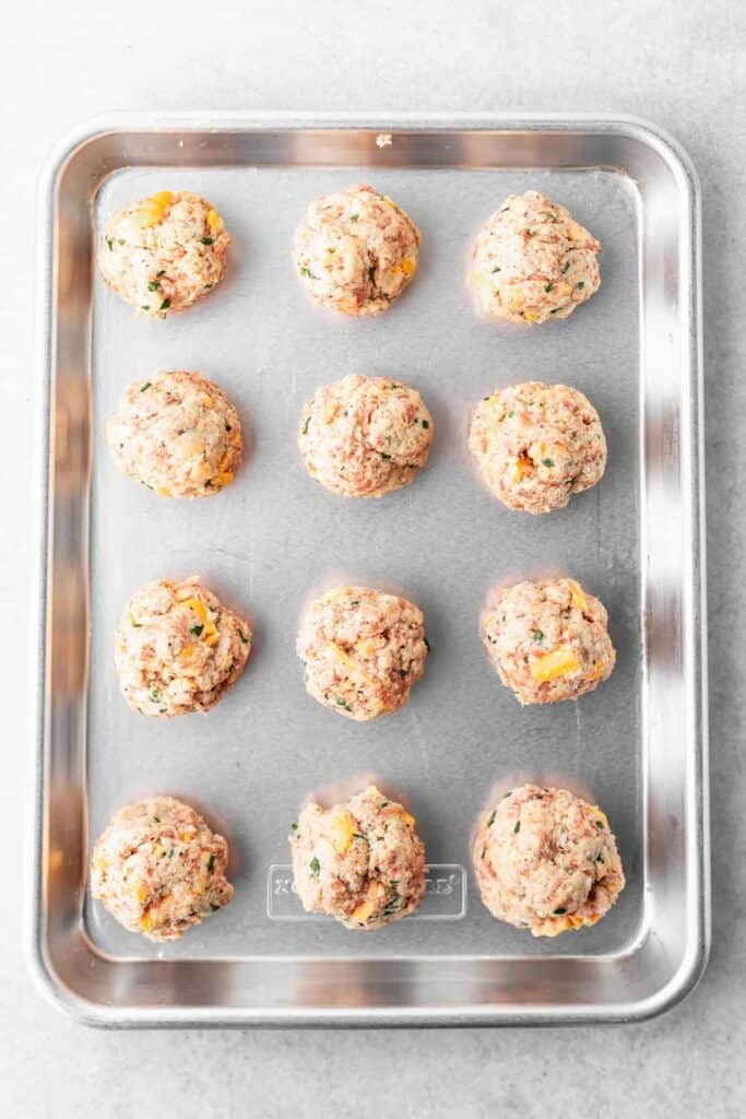 raw cream cheese sausage balls on a baking tray ready to be cooked
