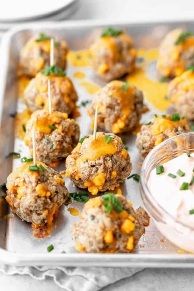 cream cheese sausage balls on a baking tray with toothpicks, ready to be dipped into garlic sauce