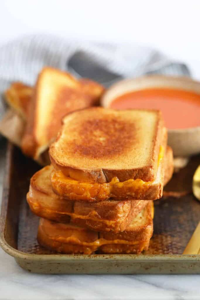sheet pan grilled cheese sandwiches next to a bowl of tomato soup