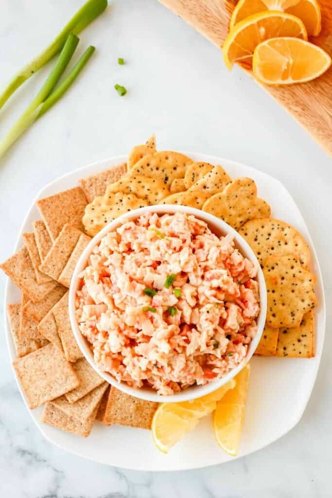 Crab dip in a bowl surrounded by carackers.