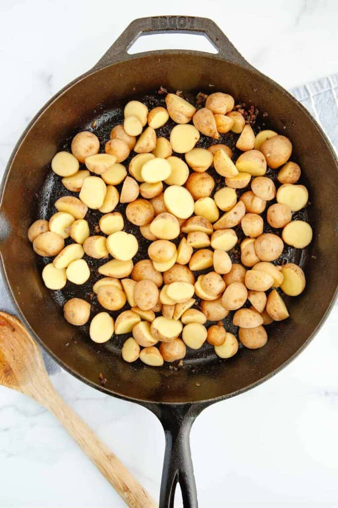 Halved baby potatoes in a cast iron pan.
