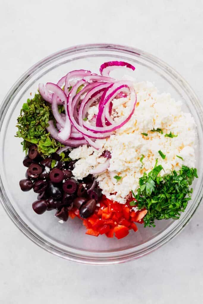 olives, pepper, mint, parsley, feta, and onion in bowl