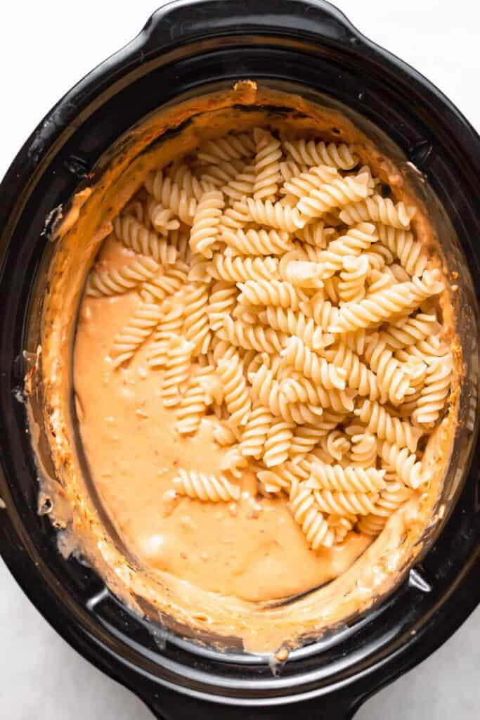 Noodles and queso dip in a slow cooker.