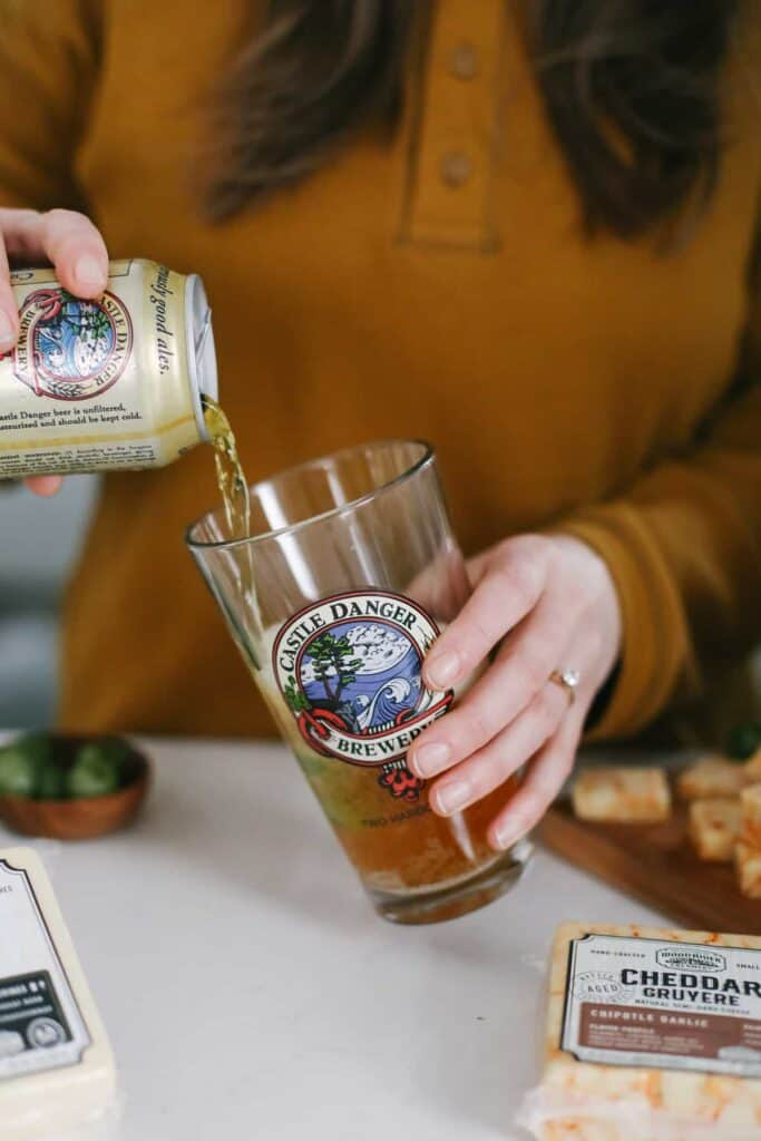 Castle Danger beer being poured into a glass with green olives