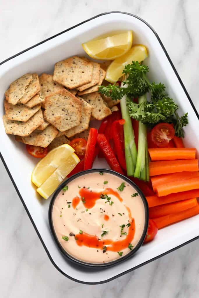 whipped cottage cheese dip in a bowl with veggies and crackers around it ready to be dipped in