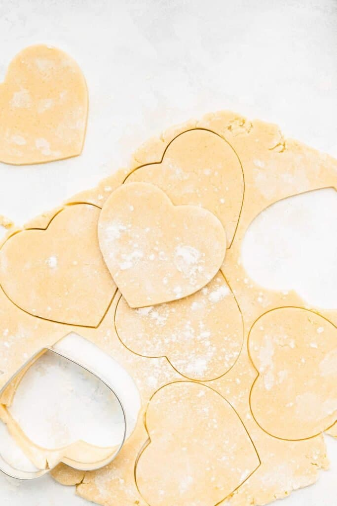 cream cheese heart cookie dough cut out into hearts with a cookie cutter