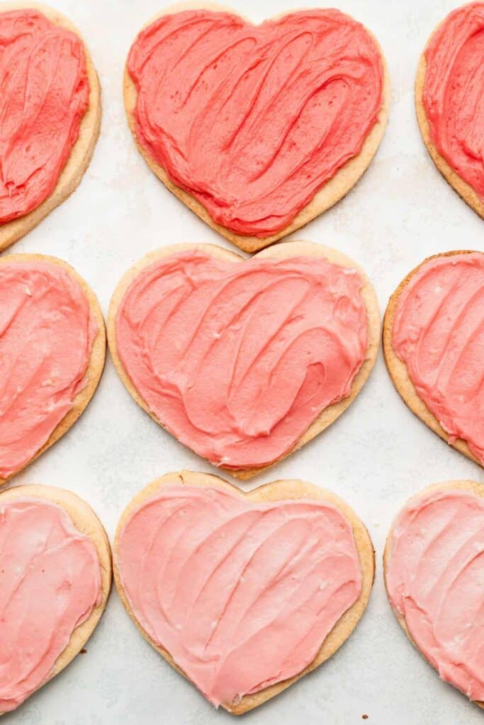 cream cheese heart cookies frosted with various shades of pink frosting