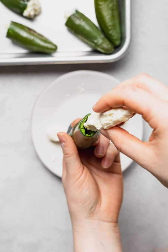 Stuffing a Jalapeño with cheese.