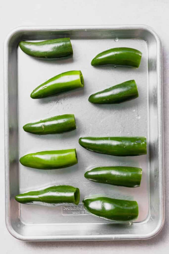 Hallowed out Jalapeño Poppers on baking sheet.