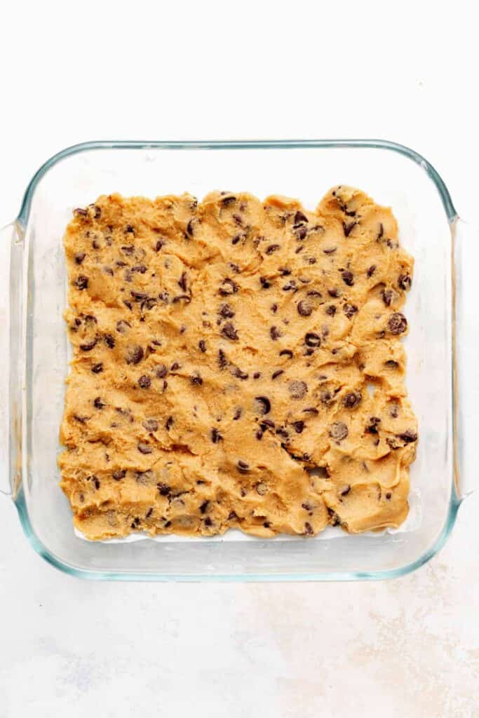 Chocolate chip cookie dough spread out on the bottom of an 8x8-inch baking pan.