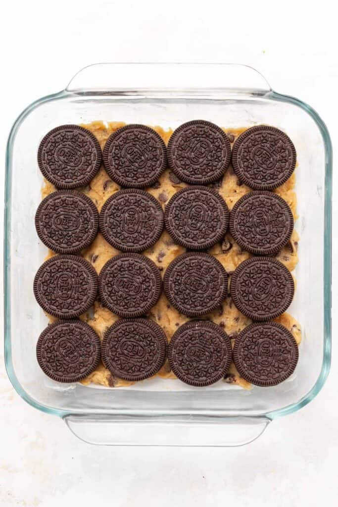 Oreos stacked on top of a cookie dough crust.