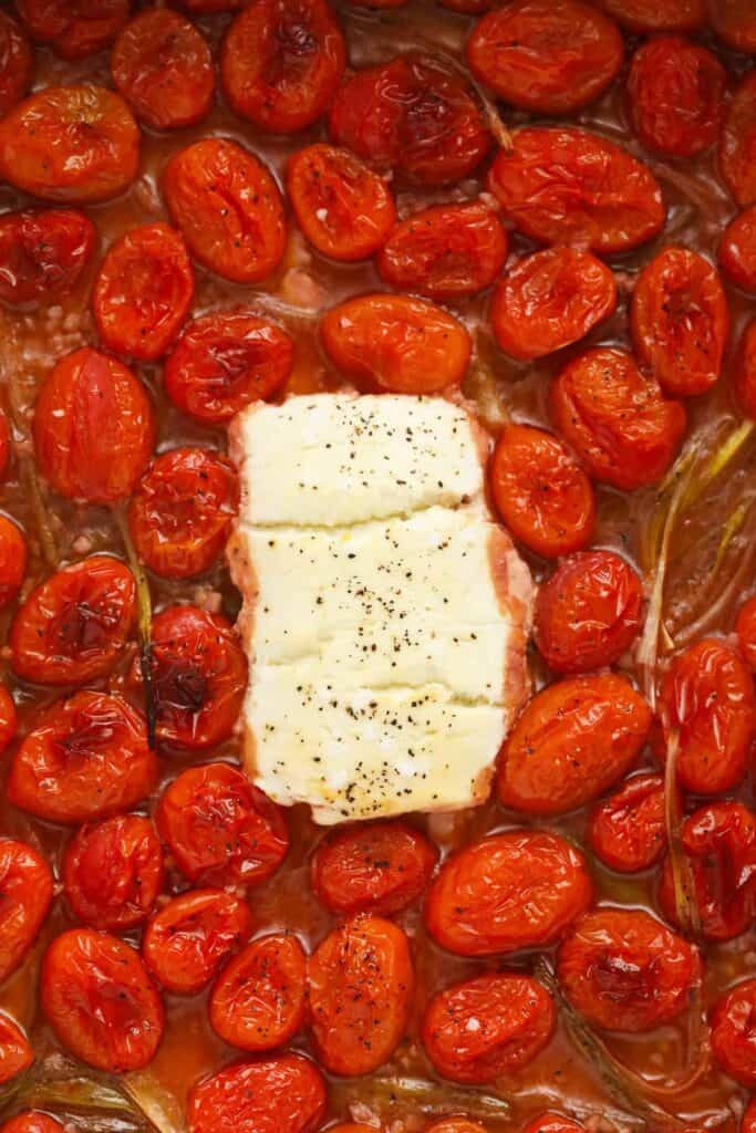 Baked goat cheese surrounded by tomatoes.