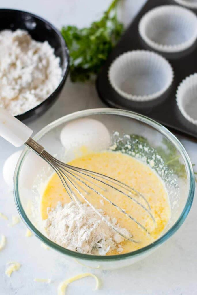 savory cheese muffins wet ingredients being mixed with dry ingredients