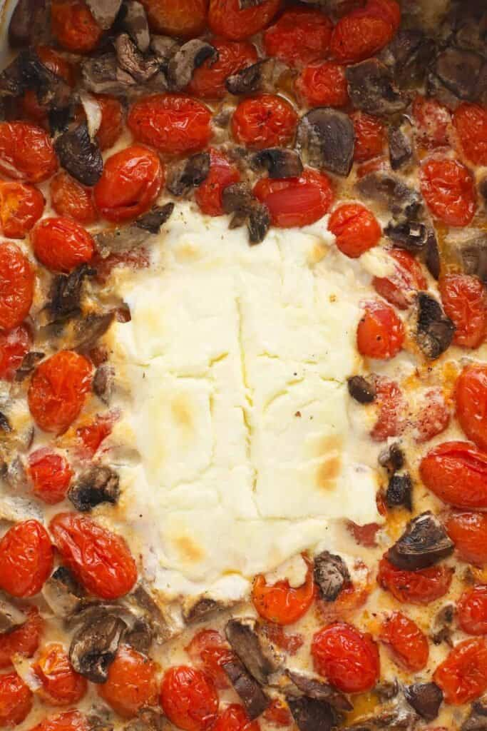 baked cream cheese surrounded by tomatoes and mushrooms after being baked