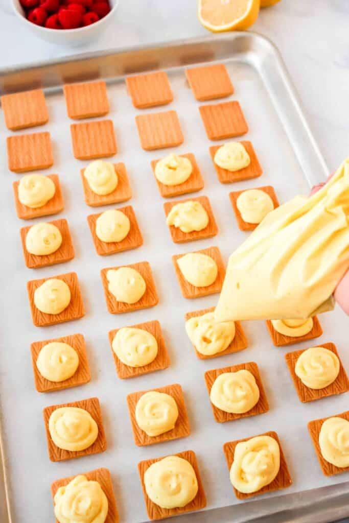 piping lemon filling onto shortbread cookies