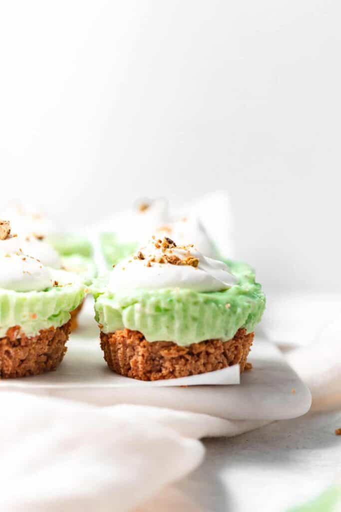 pistachio pie cups with a dollop of whip and sprinkle of pistachios on top