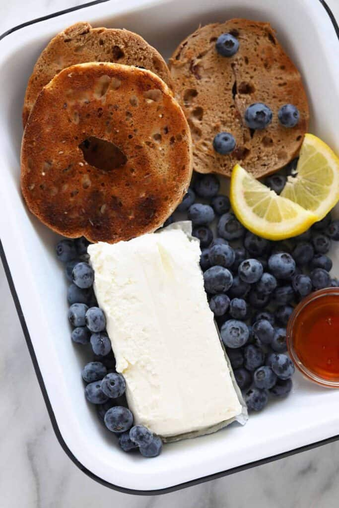 A tray of cream cheese, bagels, and blueberries.