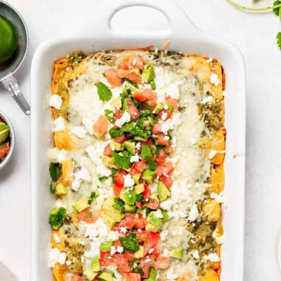 Chicken enchiladas in a casserole dish.