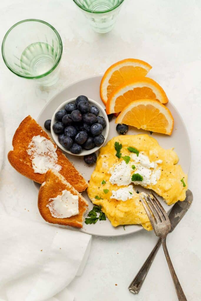 Goat cheese scrambled eggs on a plate with toast, blueberries, and oranges.