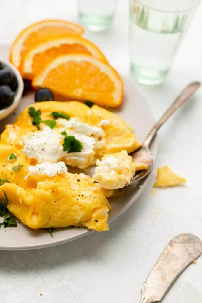 Goat cheese soft scrambled eggs on a plate.