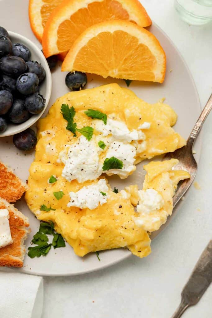 Goat cheese scrambled eggs on a plate with blueberries and orange slices.