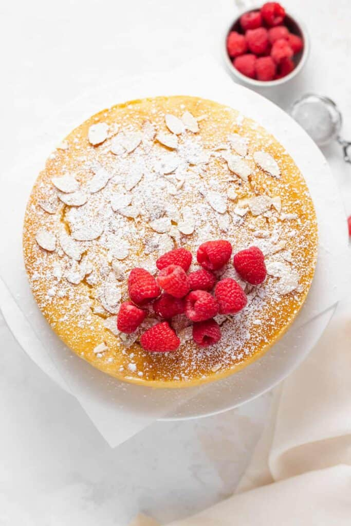 lemon ricotta cake topped with fresh berries and powdered sugar