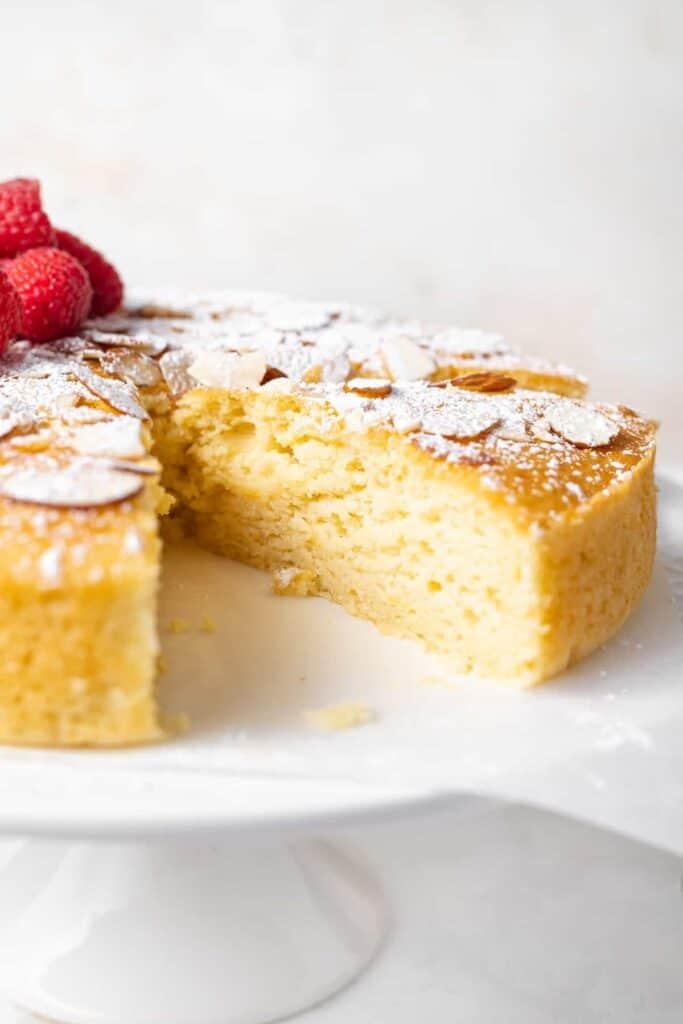 slice of lemon ricotta cake with powdered sugar and slivered almonds