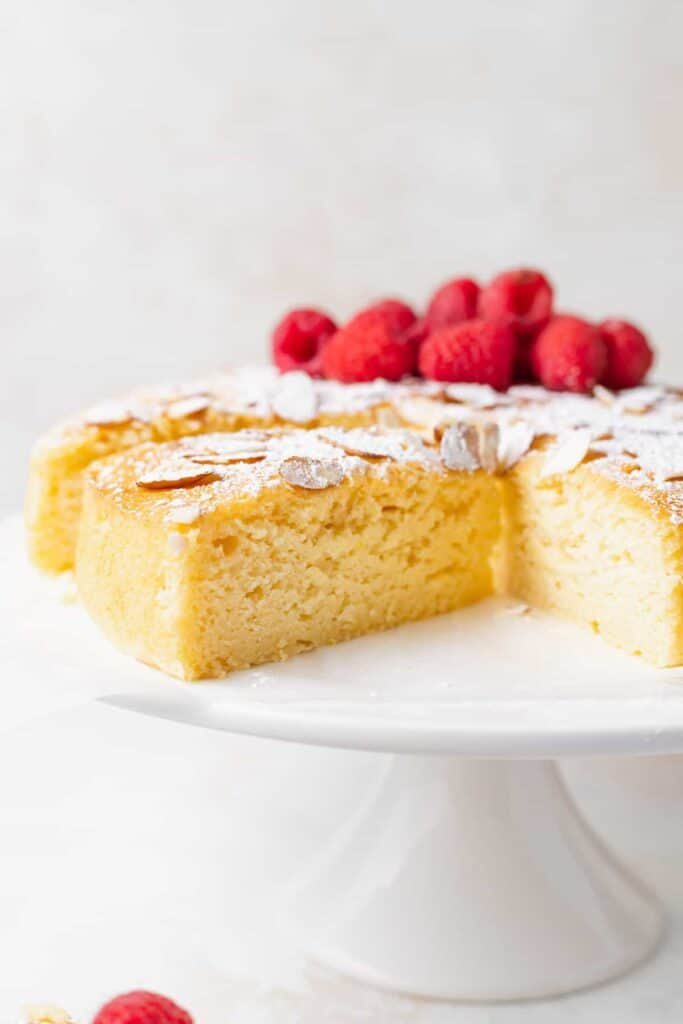 slice of lemon ricotta cake topped with powdered sugar and sliced almonds