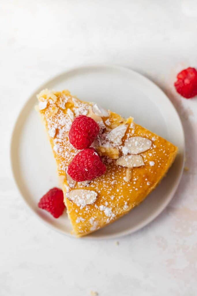 slice of lemon ricotta cake on a plate with fresh raspberries on the top